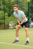 Skillful young tennis player ready to beat ball Royalty Free Stock Photography