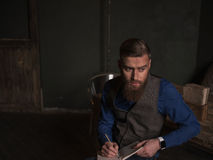Skillful young writer is creating new masterpiece. Talented bearded poet is writing a poem. He is sitting near the table and looking sideways pensively. Copy Stock Photo