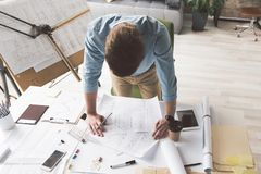 Skillful youthful man is working enthusiastically. Involved in work. Top view of qualified young architect is leaning over table with blueprints and looking at Stock Image