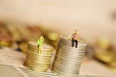 Skillnader mellan women's och men's inkomst eller lönbegrepp med miniatyrkonturer på bunt av mynt arkivfoto