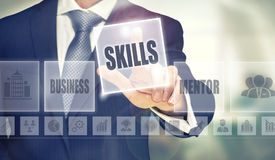 Skills Concept. Businessman pressing an Skills concept button royalty free stock photography