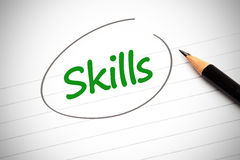 Skills word written in green on a notepad Stock Photos