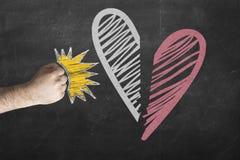 Skilsmässaförhållandebegrepp näven slår hjärta och avbrott den mot den svart tavlan Arkivfoto