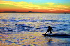 Skim Boarder. The sun starting to set on Balboa Pier in Newport Beach in California with a young skimboarder is enjoying a wave Stock Images