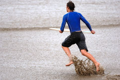 Skim Boarder at the Beach. A teenage boy runs and skims through the waves with his skimboard Stock Photo