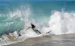 Skim Boarder riding a shore break wave at Aliso Beach in Laguna Beach, California. Royalty Free Stock Photography