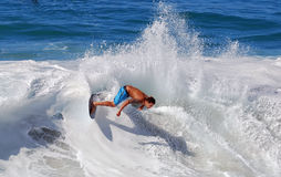 Skim Boarder riding a shore break wave at Aliso Beach in Laguna Beach, California. Stock Image