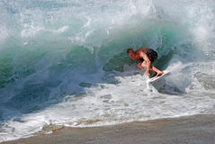 Skim Boarder riding a shore break wave at Aliso Beach in Laguna Beach, California. Stock Photography