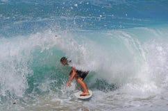 Skim Boarder riding a shore break wave at Aliso Beach in Laguna Beach, California. Image shows a skim boarder riding a shore break wave Aliso Beach in Laguna Stock Photography