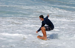 Skim Boarder riding toward a shore break wave at Aliso Beach in Laguna Beach, California. Image shows a skim boarder gliding on the water surface and toward a Royalty Free Stock Photography