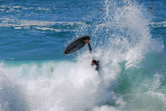 Skim Boarder wiping out while riding a shore break wave at Aliso Beach in Laguna Beach, California. Image shows a skim boarder wiping out while riding a shore Royalty Free Stock Photography