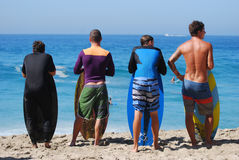 Skim Boarders wait for a wave to ride at Aliso Beach in Laguna Beach, California. Image shows skim boarders waiting for a shore break wave to ride at Aliso stock photo