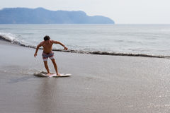 Skim boarding in Costa Rica. Young man skim boarding in Playa Cabuyal, Costa Rica on a a smoky day due to prescribed burns in the area Royalty Free Stock Photo