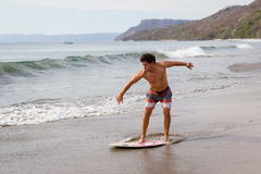 Skim boarding in Costa Rica. Young man skim boarding in Playa Cabuyal, Costa Rica on a a smoky day due to prescribed burns in the area Royalty Free Stock Image