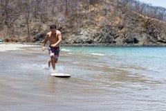 Skim boarding in Costa Rica. Young man skim boarding in Playa Calzon de Pobre, Costa Rica on a beautiful sunny day Stock Photo