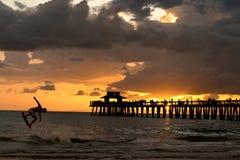 Skimboard en la puesta del sol foto de archivo