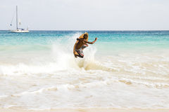 Skimboarder jumping wave. A young skimboarder performs a spectacular jump from a wave in the cape verde islands Stock Images
