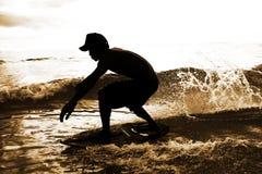 Skimboarder nelle gocce dell'acqua Fotografie Stock