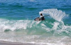 Skimboarder på den Aliso stranden, Laguna Beach, CA Arkivbild