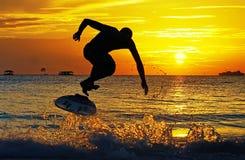 skimboarding在日落-海浪在博拉凯菲律宾踢轻碰委员会 图库摄影