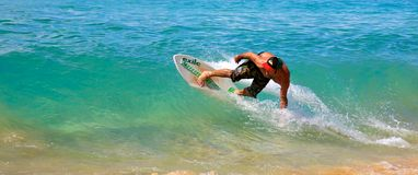 Skimboarding at Big Beach. A man skimboarding at Big Beach in Maui Hawaii. Skimboarding originated in Southern California when lifeguards wanted an easy way to Stock Images