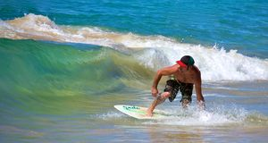 Skimboarding at Big Beach. A man skimboarding at Big Beach in Maui Hawaii. Skimboarding originated in Southern California when lifeguards wanted an easy way to Stock Photo