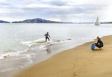 Skimboarding in San Francisco Bay, California. View of a surfer in wet suit surfing his board or skimboarding in shallow water in the San Francisco Bay, on the royalty free stock photography
