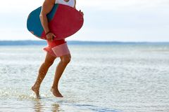 Young man with skimboard on summer beach. Skimboarding, water sport and people concept - young man with skimboard on summer beach Stock Image