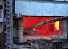 Skimming dross on melted aluminum. Skimming melted aluminum for removing the dross before casting. Aluminum foundry works showing an open furnace stock photography