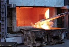 Skimming melted aluminum. For removing the dross before casting. Aluminum foundry works showing an open furnace royalty free stock image