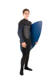 Skimming pro. Teenager in wet suit with skimboard posing isolated in white Royalty Free Stock Photos