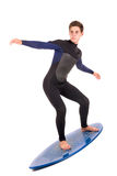Skimming pro. Teenager in wet suit with skimboard posing isolated in white Royalty Free Stock Photography