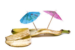 Skin of banana with umbrellas Royalty Free Stock Image