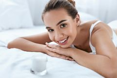 Skin Beauty. Beautiful Woman With Face Cream And Healthy Skin. Skin Beauty. Beautiful Woman With Face Cream And Healthy Soft Facial Skin Lying On White Bed royalty free stock photo