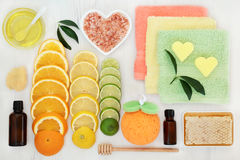 Skin and Body Care Products. With citrus fruit, honey, essential and almond oil, himalayan salt and spa accessories on white distressed background. Top view Stock Photos