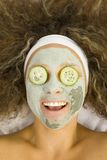 Skin care. Young happy woman with green purifying mask and cucumber's slices on eyes Stock Photos