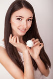 Skin Care. Beautiful healthy young woman with long hair, caring for their skin. Use cream for body care. Beauty and health Stock Image