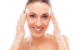 Skin care. Beautiful young woman checking her face skin and looking for blemishes Royalty Free Stock Images