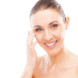 Skin care. Beautiful young woman checking her face skin and looking for blemishes Royalty Free Stock Image