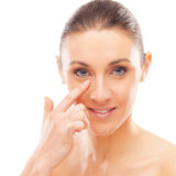 Skin care. Beautiful young woman checking her face skin and looking for blemishes Stock Photos