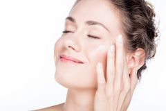 Beautiful young woman smiling and applying eye cream. Royalty Free Stock Images