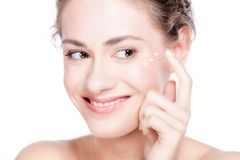 Beautiful young woman smiling and putting eye cream. Royalty Free Stock Photos