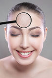 Skin care and beauty concept - face of beautiful young woman with smile over gray background. skin defect on face by loupe. Royalty Free Stock Images