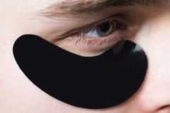 Skin care. Black pearl extract. Minimizes puffiness and reduce dark circles. Eye patches for men. Man with black eye. Patches close up. Metrosexual concept stock images