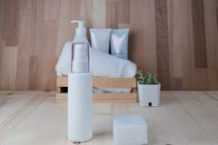 Skin care collection contain spray bottle and cotton placed on w. Ood floor. have wood basket include cream and towel with wooden wall are background. image for Stock Image
