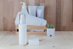Skin care collection contain spray bottle and cotton placed on w. Ood floor. have wood basket include cream and towel with wooden wall are background. image for Stock Photo
