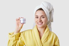 Skin care concept. Beautiful Caucasian woman going to apply moisturizing cream on face, dressed in bathrobe and towel, cares of royalty free stock photo