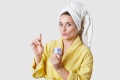 Skin care concept. Beautiful young lady holds cosmetic cream, has joyful surprised facial expression, wears yellow bathrobe, stock photo