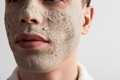 Young man is fighting first wrinkles. Skin care concept. Close up of male face with anti-aging clay mask. Guy is posing against light background. Spa and stock photo