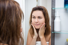 Skin care concept - happy woman looking at mirror Stock Photo